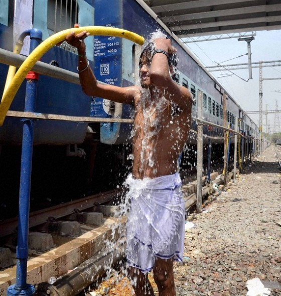 Allahabad: A man takes bath under a train water supplying pipe at a railway station in Allahabad on Saturday. Most of north India has been reeling under heat wave conditions with temperature soaring to over 46 degree Celsius. PTI Photo  (PTI5_23_2015_000094B)