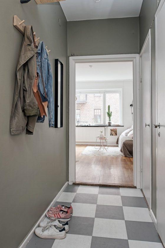 Khoảng không gian ngoài cửa vào đã được chủ nhà tận dụng để lắp một mẫu gương nhỏ và giá treo quần áo .